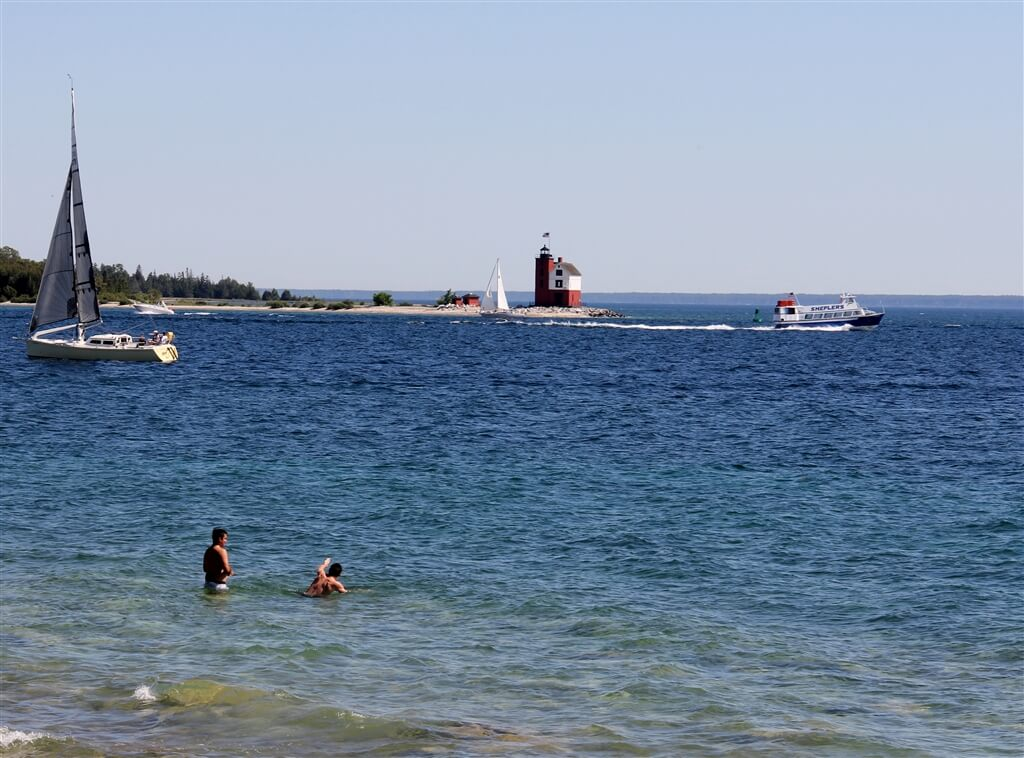 Photo of swimmers in the mouth of Mackinac Island Harbor viewing the Round Island Lighthouse. © 2016 Frank Rogala.