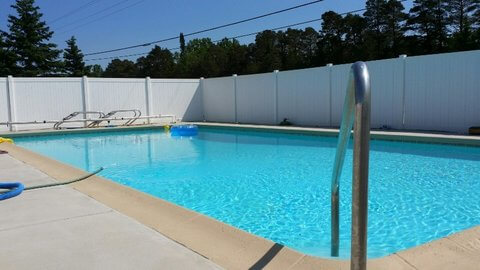 View of heated pool near hotel rooms with large privacy fence. © Frank Rogala.