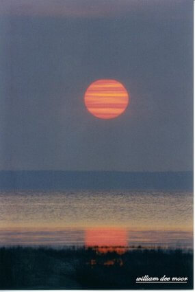 Photo of sunrise over the bay by Bill Moor (2004) at Mackinaw Mill Creek Camping in Mackinaw City, MI.