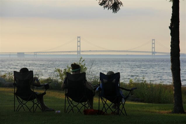 Photo of camper reading in view of the Mackinac Bridge at Mackinaw Mill Creek Camping in Mackinaw City, MI. © 2016 Frank Rogala.