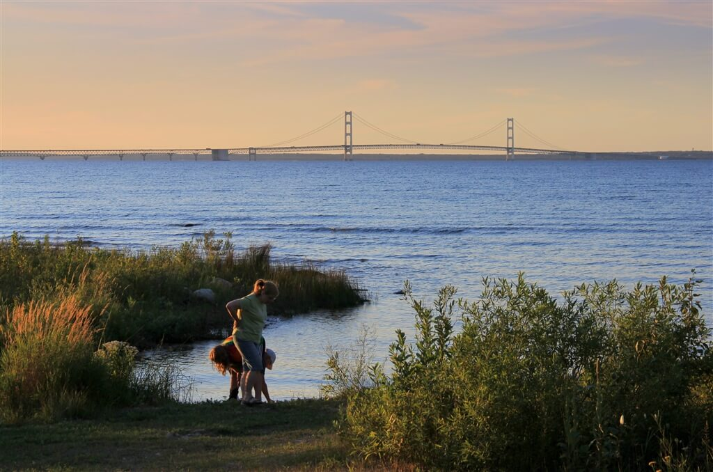 Photo of campers skipping stones with a view of the Mackinac Bridge at Mackinaw Mill Creek Camping in Mackinaw City, MI. © 2016 Frank Rogala.