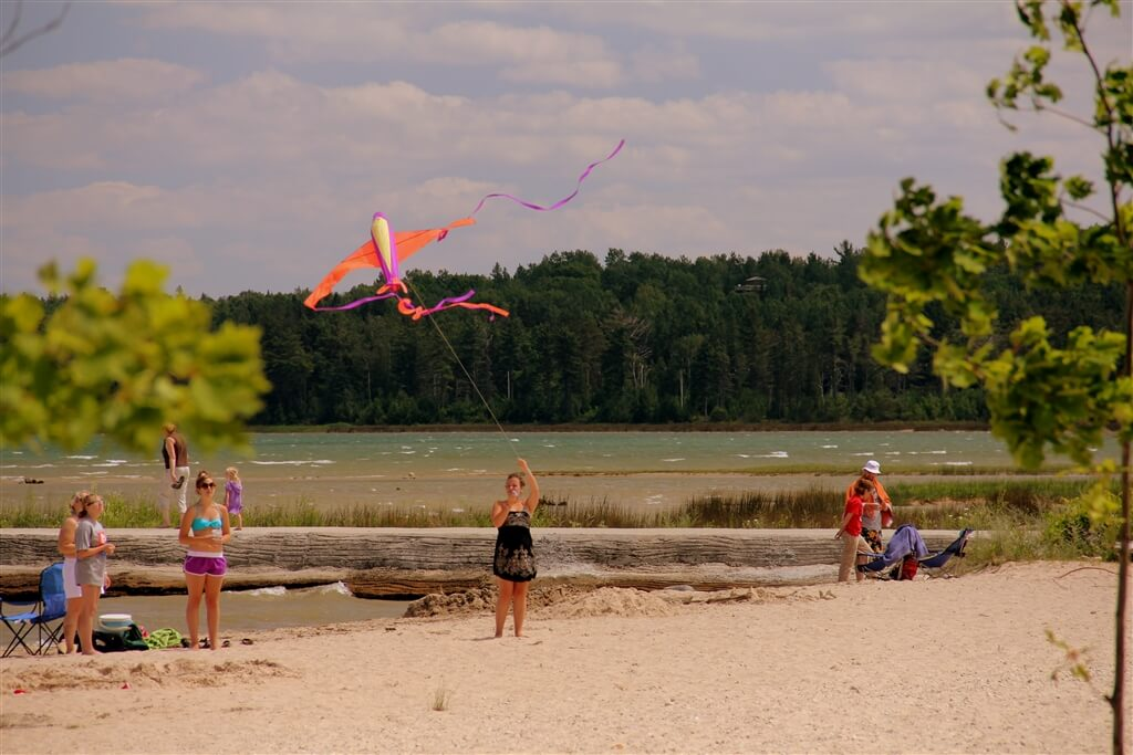 Photo of campers flying kites on the sandy beach of Mackinaw Mill Creek Camping in Mackinaw City, MI. © 2016 Frank Rogala.