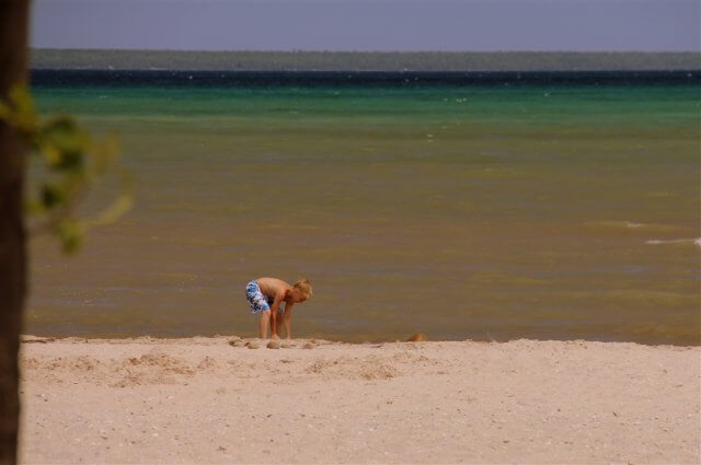 Photo of child playing on the sandy beach of Lake Huron at Mackinaw Mill Creek Camping in Mackinaw City, MI. © 2016 Frank Rogala.