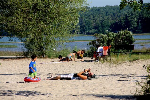 Photo of campers sunbathing on the sandy beaches of Mackinaw Mill Creek Camping in Mackinaw City, MI. © 2016 Frank Rogala.