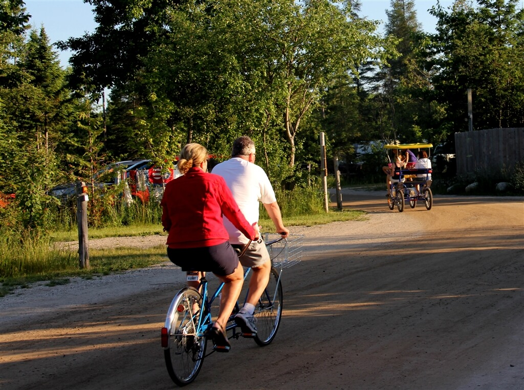 Photo of campers riding a bicycle built for two at Mackinaw Mill Creek Camping in Mackinaw City, MI. © 2016 Frank Rogala.