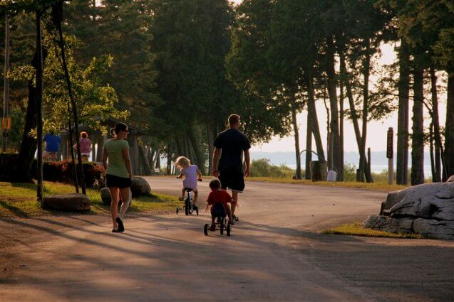 Photo of campers taking a stroll near Big Rock at Mackinaw Mill Creek Camping in Mackinaw City, MI. © 2016 Frank Rogala.