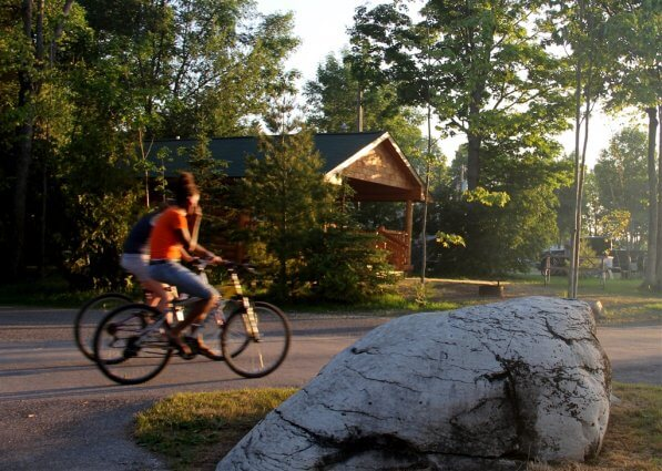 Photo of campers riding bikes near Big Rock at Mackinaw Mill Creek Camping in Mackinaw City, MI. © 2016 Frank Rogala.