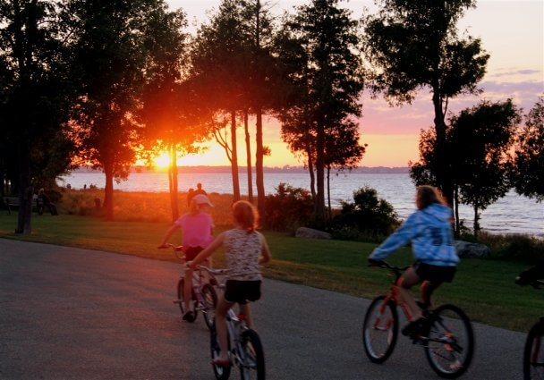 Photo of campers riding bikes at sunset at Mackinaw Mill Creek Camping in Mackinaw City, MI. © 2016 Frank Rogala.