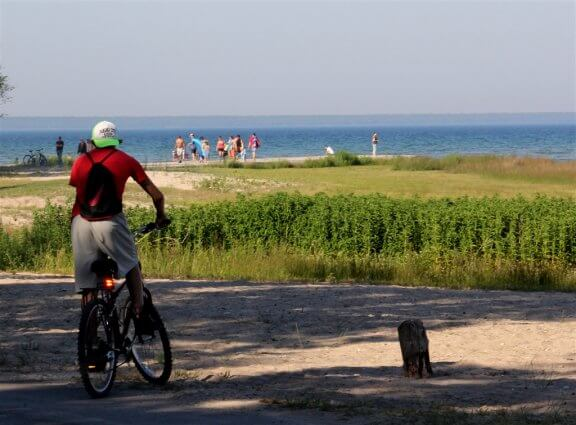 Photo of a bicylcist on the shoreline of Mackinaw Mill Creek Camping in Mackinaw City, MI. © 2016 Frank Rogala.
