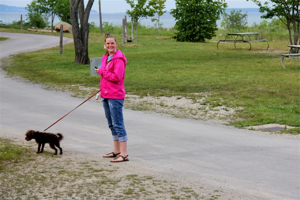 Photo of camper walking her dog on Cadottes Point at Mackinaw Mill Creek Camping in Mackinaw City, MI. © 2016 Frank Rogala.
