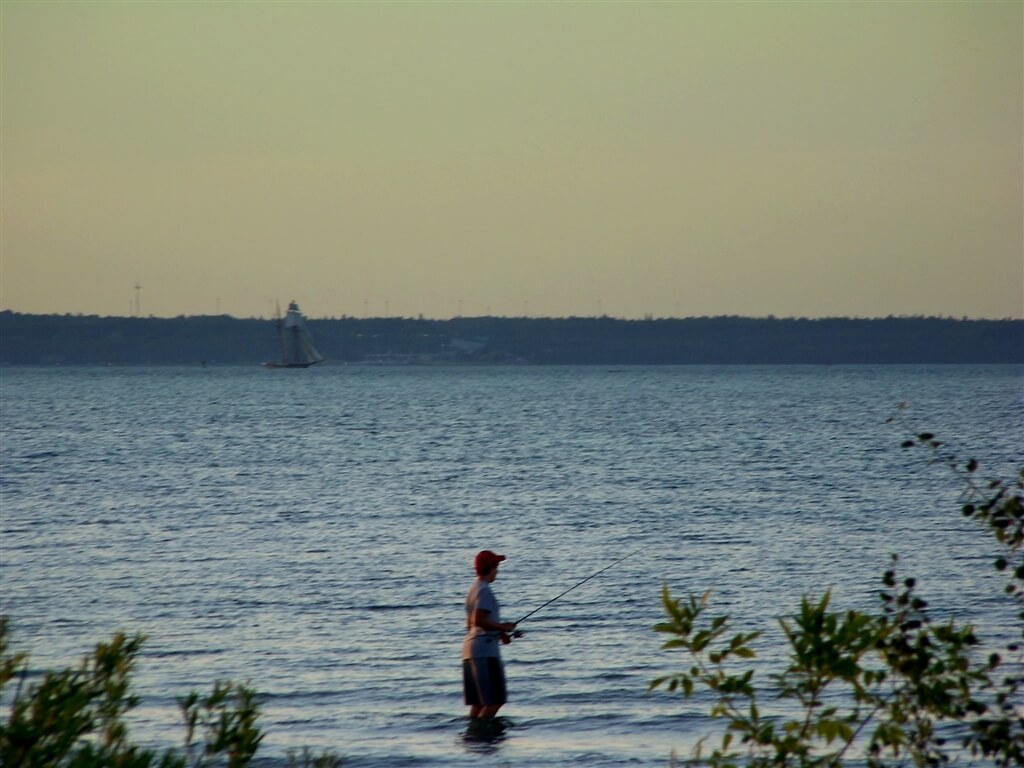 Photo of a schooner on the shore while man fishes in Lake Huron from the shores of Mackinaw Mill Creek Camping in Mackinaw City, MI. © 2016 Frank Rogala.