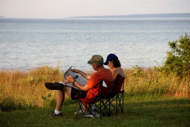 Photo of a camping couple reading the newspaper on the shores of Mackinaw Mill Creek Camping in Mackinaw City, MI. © 2016 Frank Rogala.
