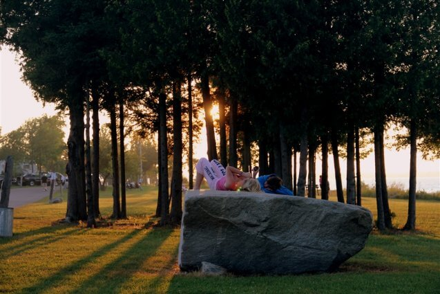 Photo of campers relaxing on a boulder at sunset at Mackinaw Mill Creek Camping in Mackinaw City, MI. © 2016 Frank Rogala.
