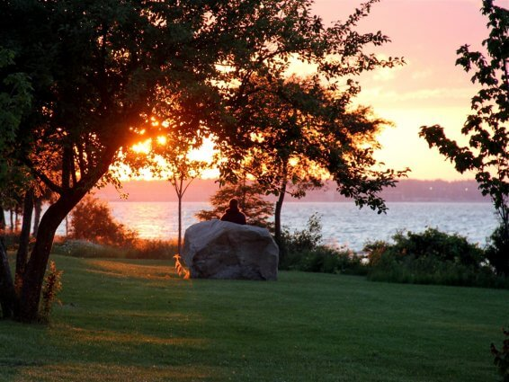 Photo of a camper by a big rock during sunset at Mackinaw Mill Creek Camping in Mackinaw City, MI. © 2016 Frank Rogala.