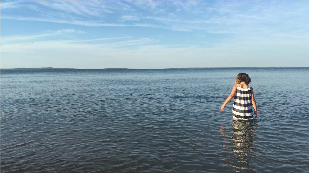 Photo of child in lake at Mackinaw Mill Creek Camping
