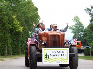 Grand Marshal on a Ford tractor at Mackinaw Mill Creek Camping's 50th Anniversary celebration parade. Copyright (©) 2014 Mackinaw Mill Creek Camping and Frank Rogala. All rights reserved.